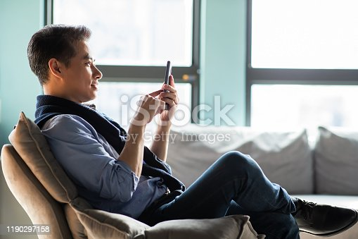 asian middle aged man use smart phone and enjoy his retirement life at home