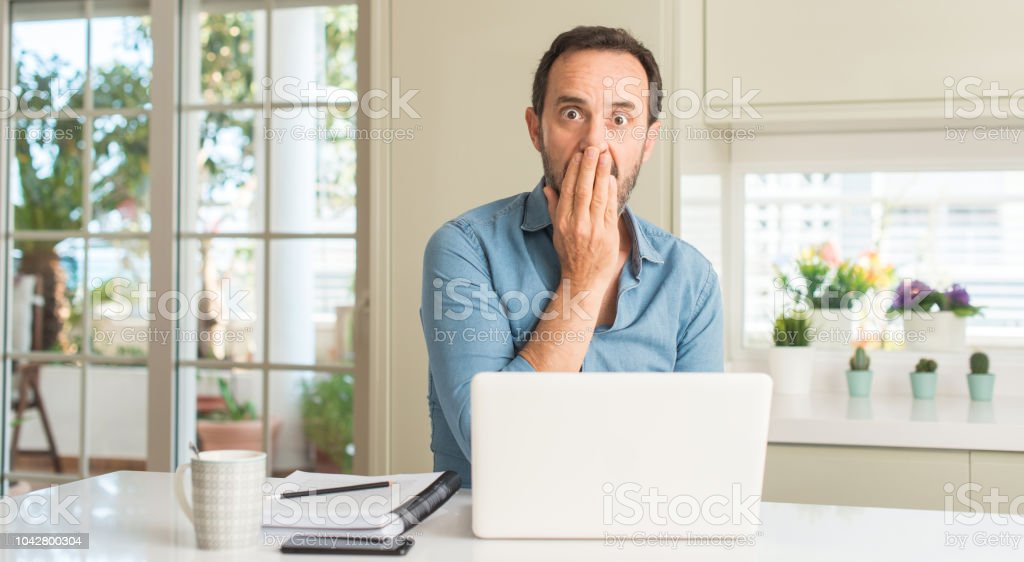 Middle age man using laptop at home cover mouth with hand shocked...