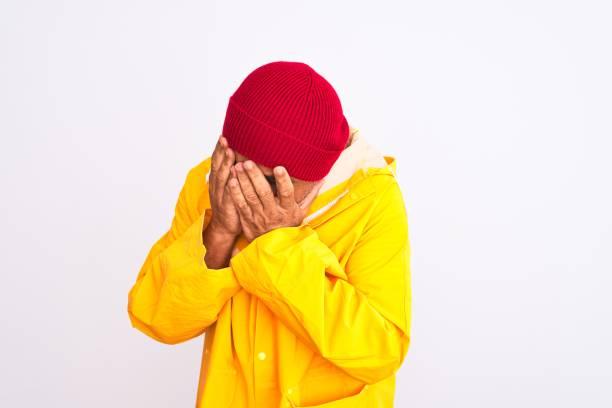 hombre de mediana edad con impermeable y sombrero de lana de pie sobre fondo blanco aislado con expresión triste cubriendo la cara con las manos mientras llora. concepto de depresión. - vergüenza fotografías e imágenes de stock