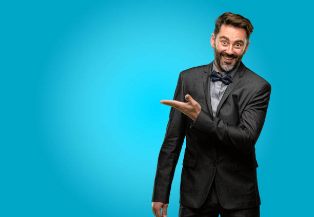 Middle age man, with beard and bow tie holding something in empty hand Middle age man, with beard and bow tie holding something in empty hand presenter stock pictures, royalty-free photos & images