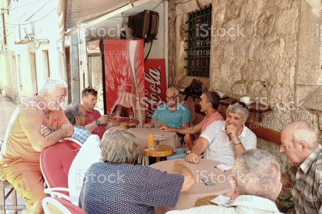 Personas de edad media están jugando a las cartas, Kotor - Montenegro - foto de stock