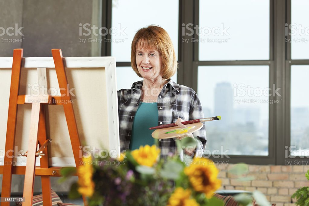Middle Age Retired Woman Hobby Painting in Loft Condominium Home royalty-free stock photo