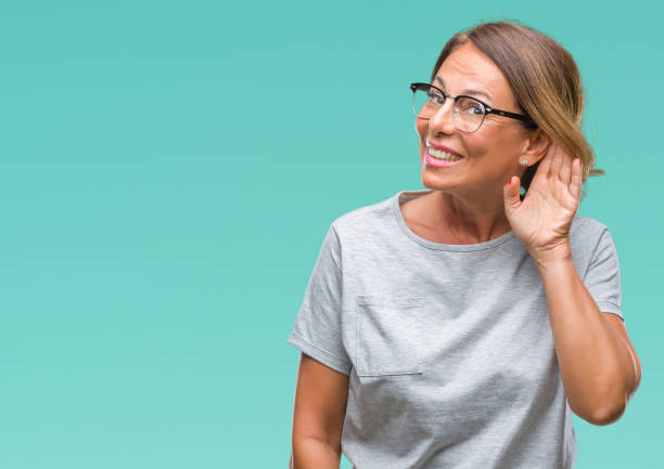 middle age senior hispanic woman wearing glasses over isolated background smiling with hand over ear listening an hearing to rumor or gossip. deafness concept. - sordità foto e immagini stock