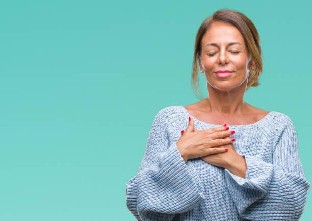 mittleres alter senior hispanic frau tragen winter pullover über isolierte hintergrund lächelnd mit händen auf brust mit geschlossenen augen und dankbar geste auf gesicht. gesundheitskonzept. - die wahrheit tut weh stock-fotos und bilder