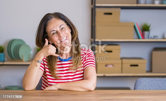 Middle age senior woman sitting at the table at home smiling doing phone gesture with hand and fingers like talking on the telephone. Communicating concepts.
