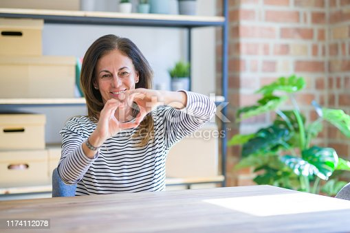 Middle age senior woman sitting at the table at home smiling in love doing heart symbol shape with hands. Romantic concept.