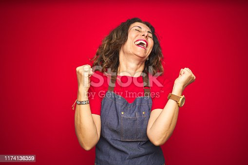 Middle age senior woman wearing apron uniform over red isolated background celebrating surprised and amazed for success with arms raised and eyes closed. Winner concept.