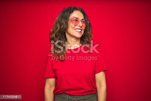 Middle age senior woman wearing cute heart shaped glasses over red isolated background looking away to side with smile on face, natural expression. Laughing confident.