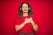 Middle age senior woman wearing headphones listening to music over red isolated background smiling with hands on chest with closed eyes and grateful gesture on face. Health concept.
