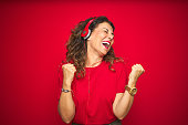istock Middle age senior woman wearing headphones listening to music over red isolated background very happy and excited doing winner gesture with arms raised, smiling and screaming for success. Celebration concept. 1174131779