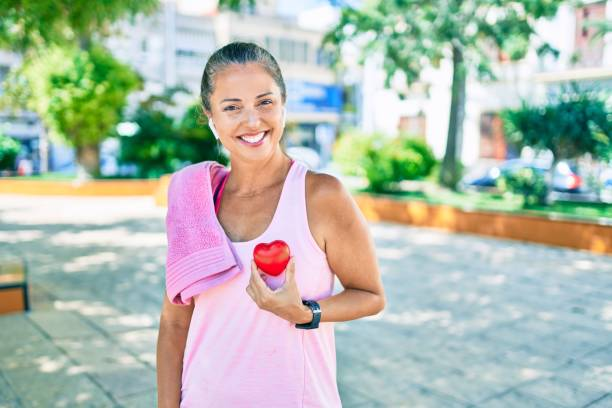 Middle age sportswoman asking for health care holding heart at the park Middle age sportswoman asking for health care holding heart at the park healthy heart stock pictures, royalty-free photos & images