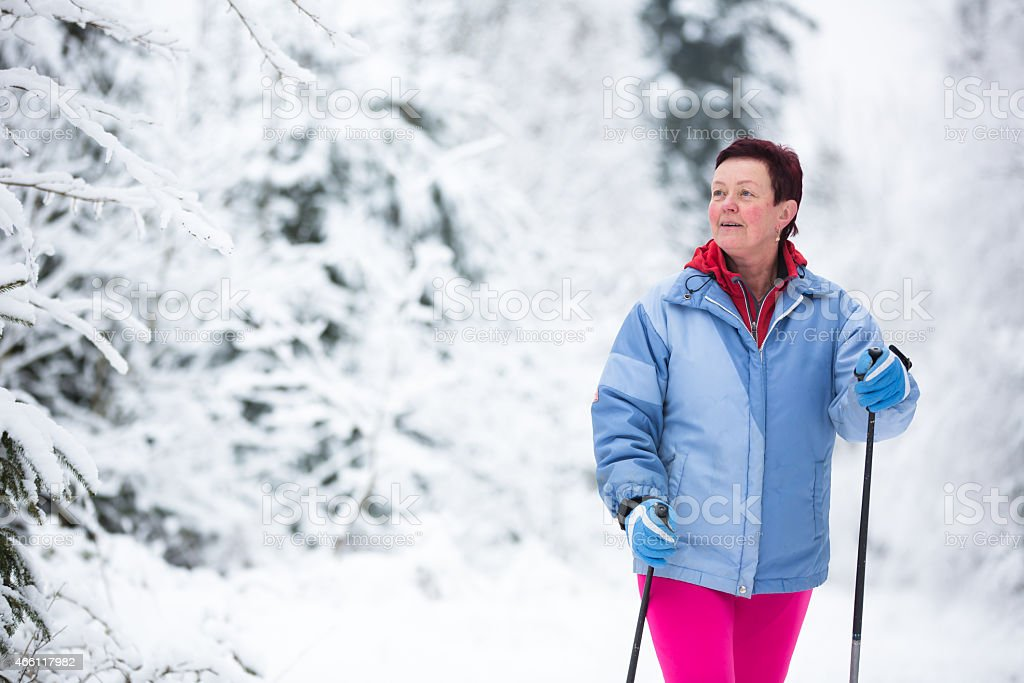 Middle age woman cross-country skiing stock photo