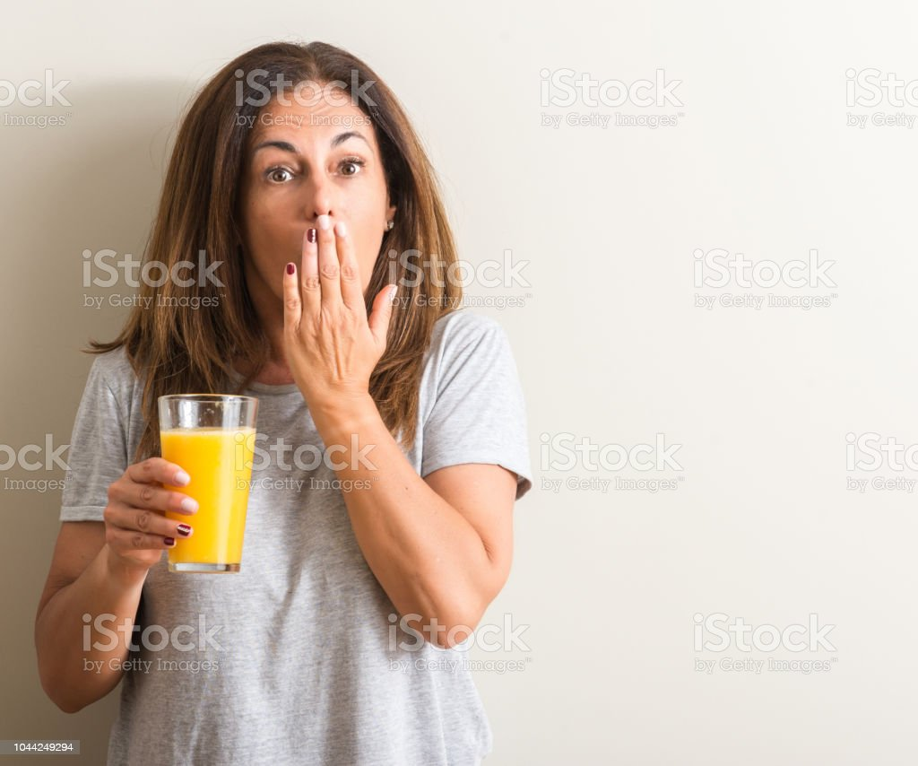 Middle Age Woman Drinking Orange Juice In A Glass Cover