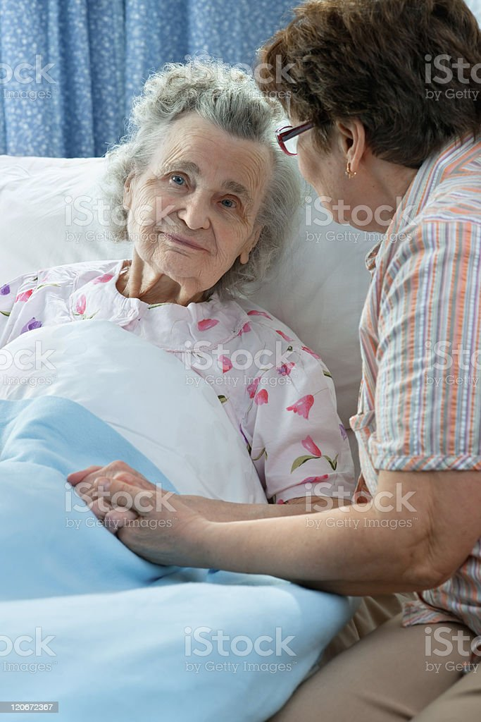Middle age woman holding elderly womans hand in hospital bed stock photo