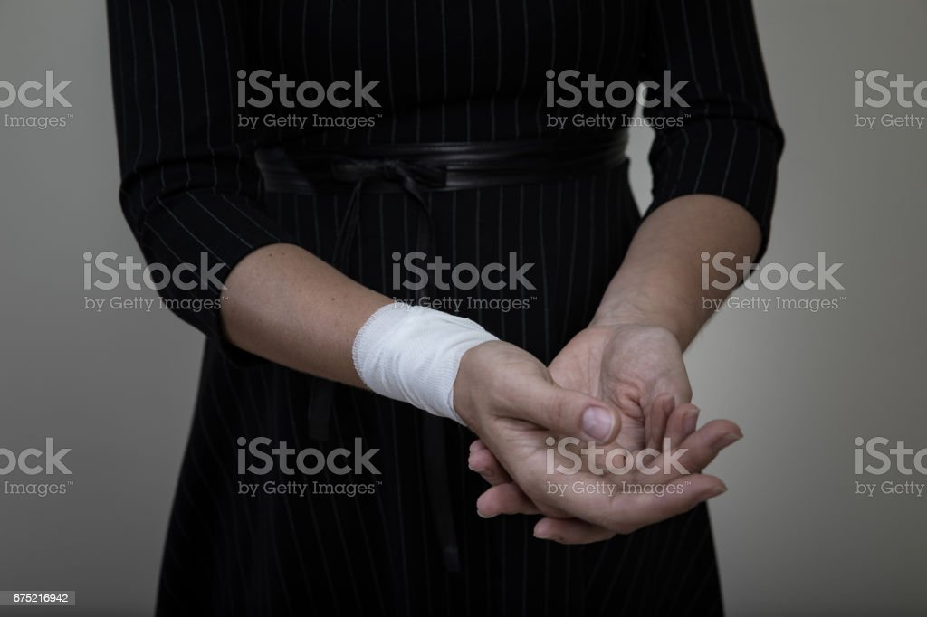 Middle age woman showing her bandaged wrist. stock photo