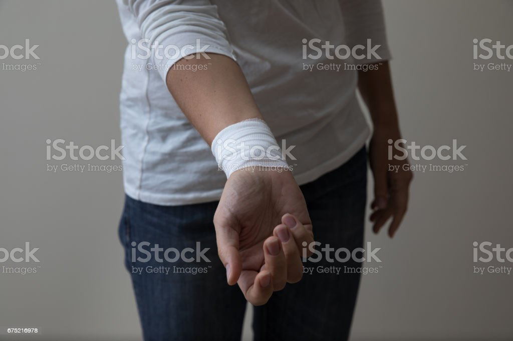 Moyen age femme montrant son poignet bandé. - Photo