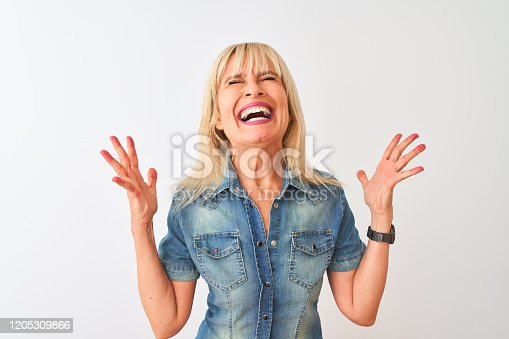 587932042istockphoto Middle age woman wearing casual denim shirt standing over isolated white background celebrating mad and crazy for success with arms raised and closed eyes screaming excited. Winner concept 1205309866