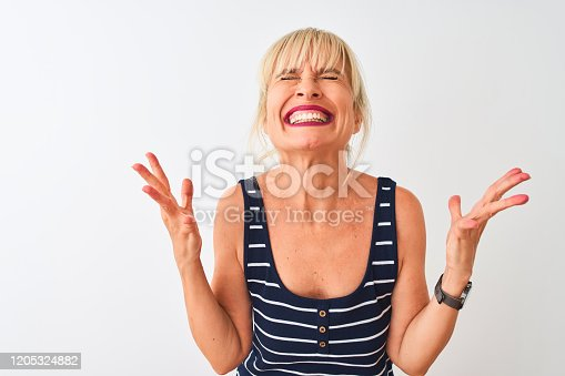 587932042istockphoto Middle age woman wearing casual striped t-shirt standing over isolated white background celebrating mad and crazy for success with arms raised and closed eyes screaming excited. Winner concept 1205324882