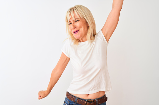 Middle age woman wearing casual t-shirt standing over isolated white background Dancing happy and cheerful, smiling moving casual and confident listening to music