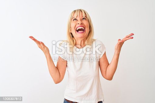 587932042istockphoto Middle age woman wearing casual t-shirt standing over isolated white background celebrating mad and crazy for success with arms raised and closed eyes screaming excited. Winner concept 1205307812
