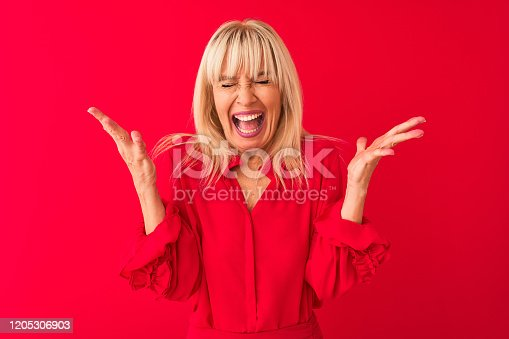 587932042istockphoto Middle age woman wearing elegant shirt standing over isolated red background celebrating mad and crazy for success with arms raised and closed eyes screaming excited. Winner concept 1205306903