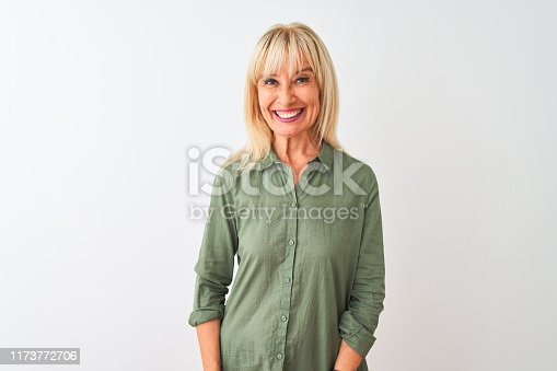 Middle age woman wearing green casual shirt standing over isolated white background with a happy and cool smile on face. Lucky person.