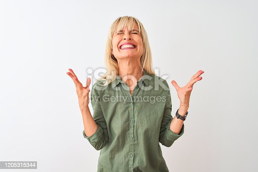 587932042istockphoto Middle age woman wearing green casual shirt standing over isolated white background celebrating mad and crazy for success with arms raised and closed eyes screaming excited. Winner concept 1205315344