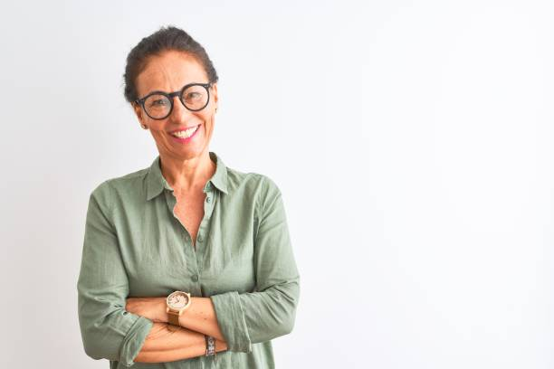 Middle age woman wearing green shirt and glasses standing over isolated white background happy face smiling with crossed arms looking at the camera. Positive person. Middle age woman wearing green shirt and glasses standing over isolated white background happy face smiling with crossed arms looking at the camera. Positive person. spanish and portuguese ethnicity stock pictures, royalty-free photos & images