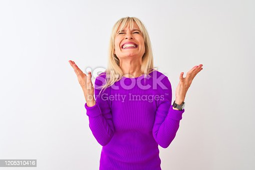 587932042istockphoto Middle age woman wearing purple t-shirt standing over isolated white background celebrating mad and crazy for success with arms raised and closed eyes screaming excited. Winner concept 1205310416