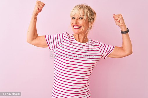 istock Middle age woman wearing striped t-shirt standing over isolated pink background showing arms muscles smiling proud. Fitness concept. 1173773407