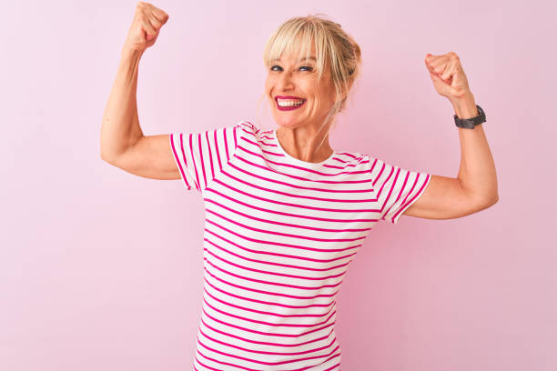 middle age woman wearing striped t-shirt standing over isolated pink background showing arms muscles smiling proud. fitness concept. - muscolo foto e immagini stock