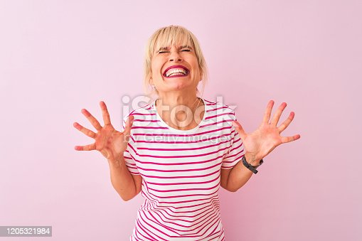 587932042istockphoto Middle age woman wearing striped t-shirt standing over isolated pink background celebrating mad and crazy for success with arms raised and closed eyes screaming excited. Winner concept 1205321984