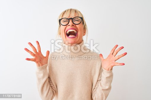 587932042istockphoto Middle age woman wearing turtleneck sweater and glasses over isolated white background celebrating mad and crazy for success with arms raised and closed eyes screaming excited. Winner concept 1173773100