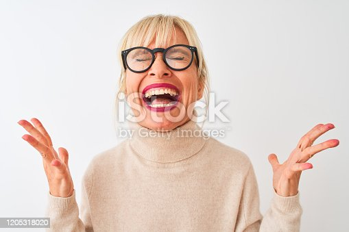 587932042istockphoto Middle age woman wearing turtleneck sweater and glasses over isolated white background celebrating mad and crazy for success with arms raised and closed eyes screaming excited. Winner concept 1205318020