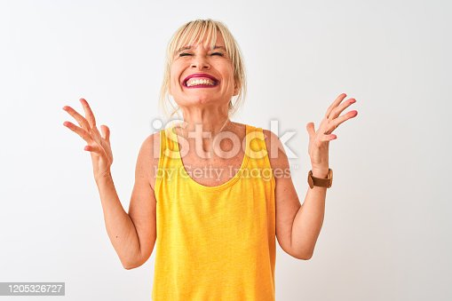 587932042istockphoto Middle age woman wearing yellow casual t-shirt standing over isolated white background celebrating mad and crazy for success with arms raised and closed eyes screaming excited. Winner concept 1205326727