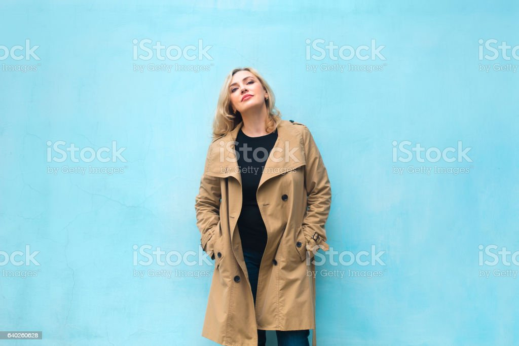 Middle age women near blue wall. Happiness concept. stock photo