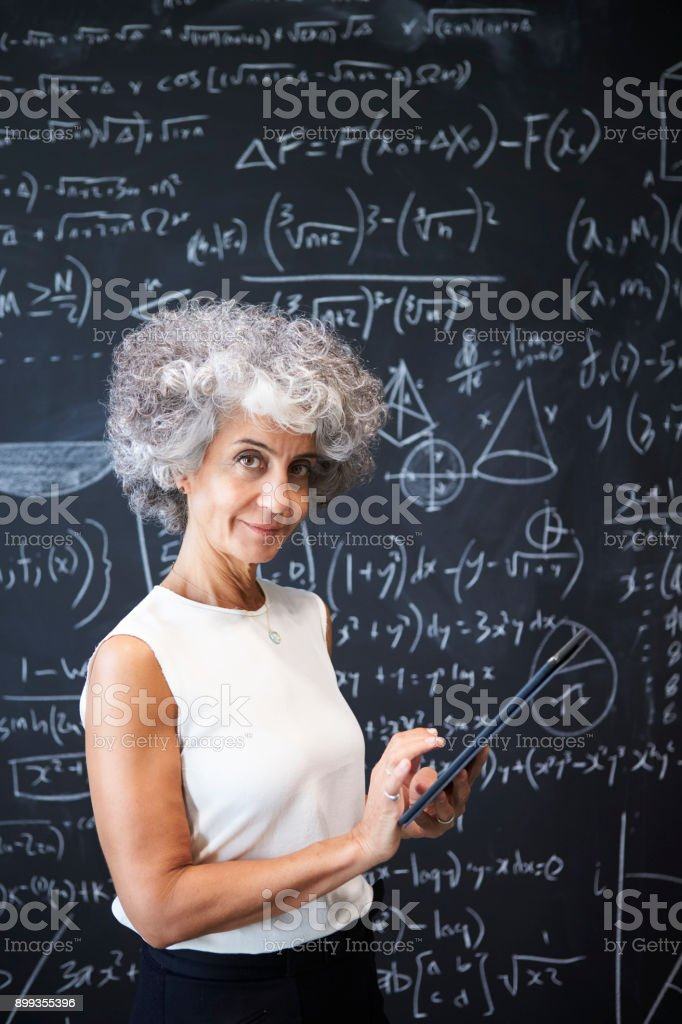 Middle aged academic woman at blackboard smiling to camera stock photo