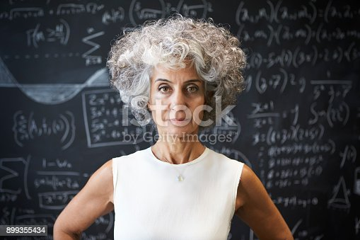 istock Middle aged academic woman standing in front of blackboard 899355434
