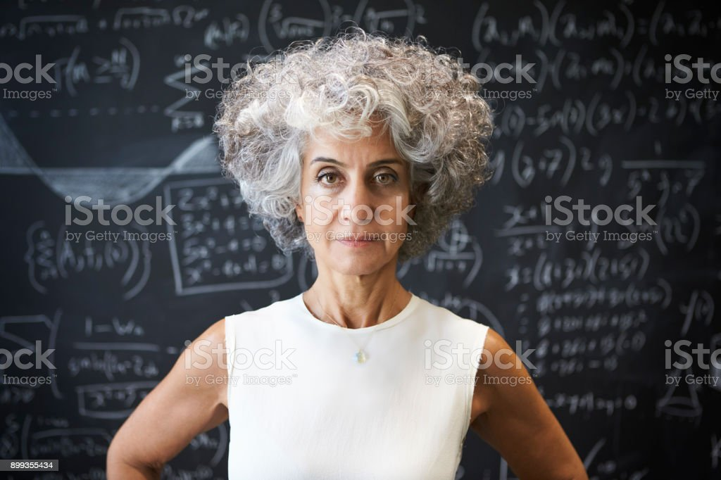 Middle aged academic woman standing in front of blackboard stock photo
