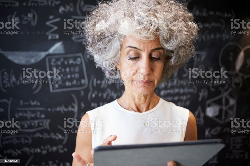 Middle aged academic woman using tablet, close up stock photo