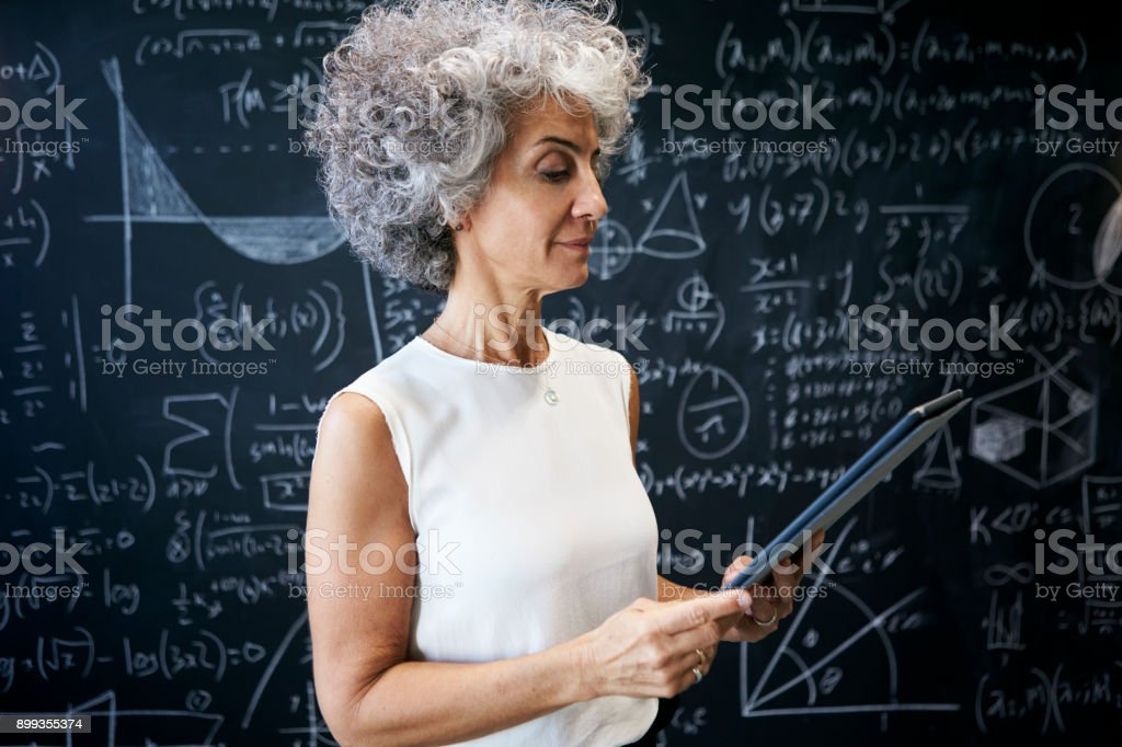 Middle aged academic woman working at blackboard stock photo