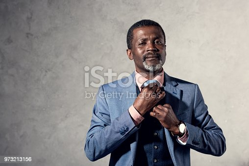 973213156 istock photo middle aged african american man fixing tie 973213156