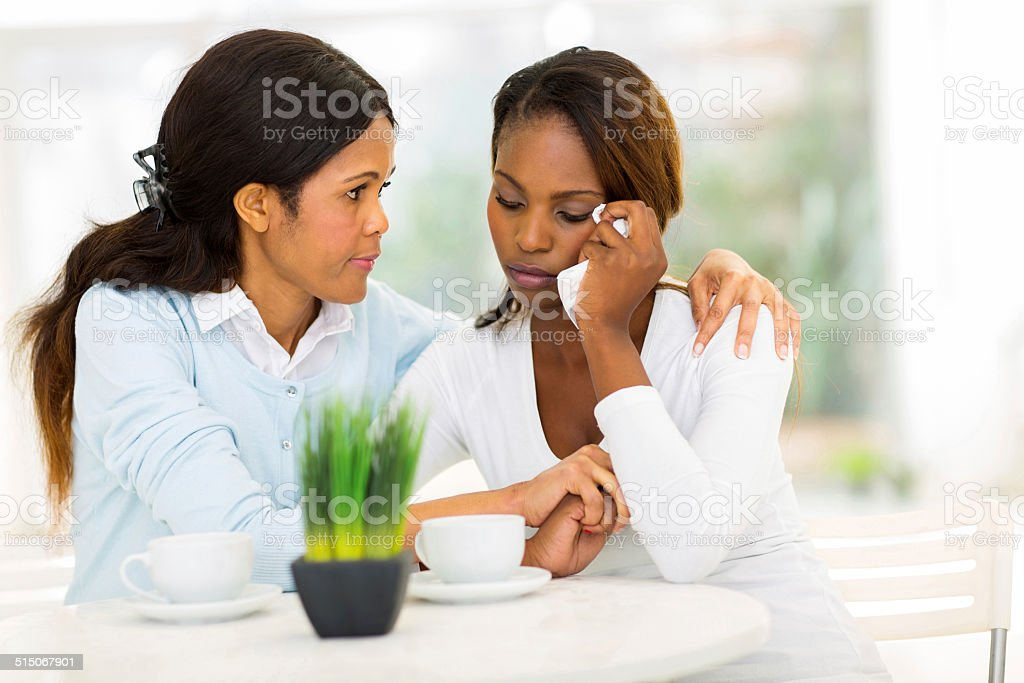 middle aged african woman comforting her daughter stock photo