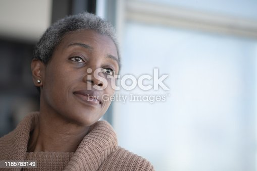 A beautiful, middle aged African woman rests her head against a window as she leans against it with her back.  She has a neutral expression on her face as she is deep in thought and reflection.  She is wearing a casual and comfortable sweater in this head shot.