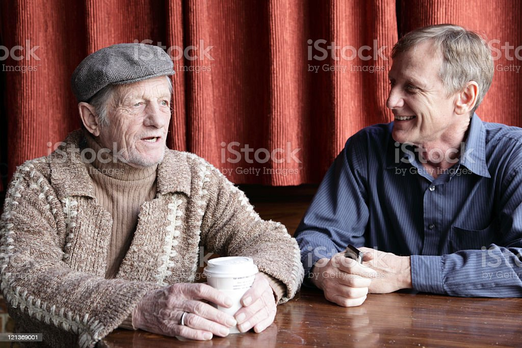 A middle aged and an elderly man meeting for coffee royalty-free stock photo