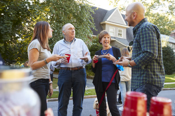 middle aged and senior neighbours talking at a block party - vicino foto e immagini stock