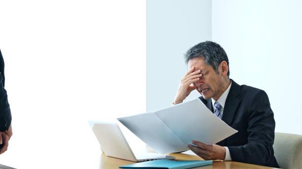 中年のアジア人ビジネスマンが部下から報告を受ける。 - people of color ストックフォトと画像