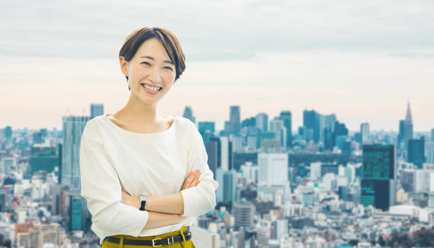 Middle aged asian businesswoman in front of the city. Middle aged asian businesswoman in front of the city. japanese ethnicity stock pictures, royalty-free photos & images