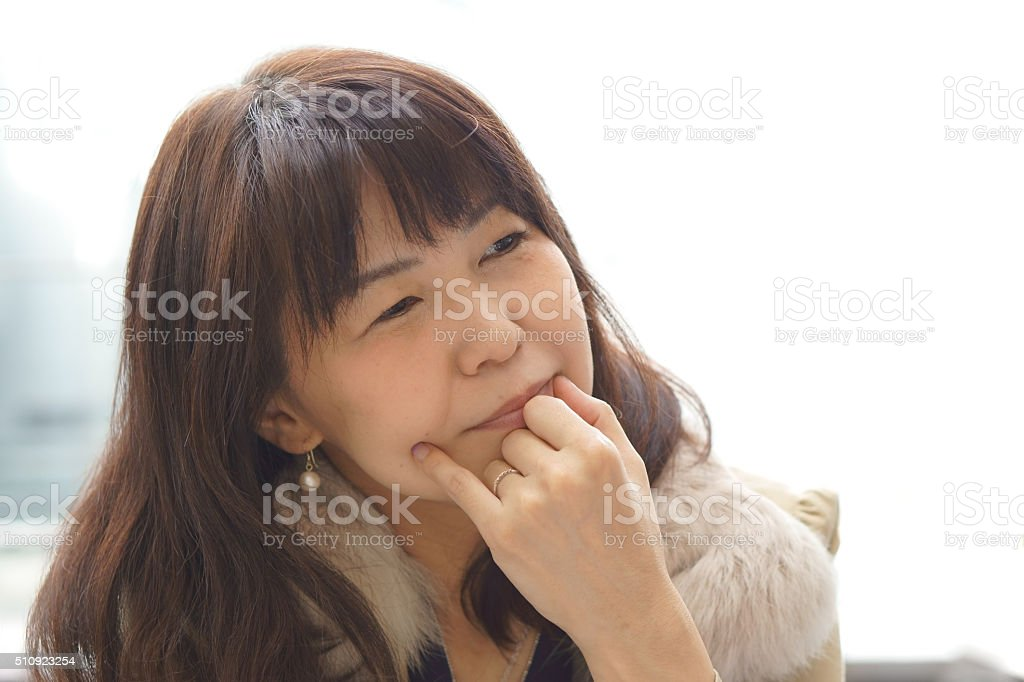 middle aged Asian woman contemplating stock photo