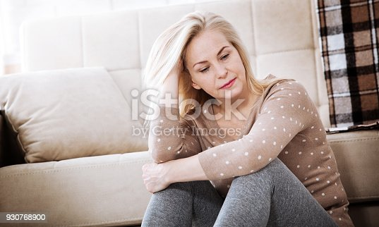 istock Middle aged barefoot woman sitting at the floor embracing her knees, near sofa at home, her head down, bored, troubled with domestic violence. 930768900